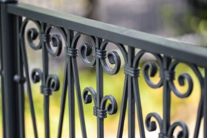 a gray wrought iron fence is a great addition to a home