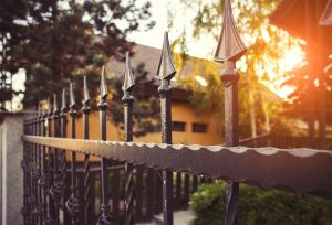 Exquisite wrought iron fence guarding a property with the sun aligning the horizon behind silhouette of trees and leaves.
