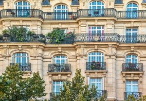 Street view of an old, elegant residential building facade in Paris, with ornate details in the stone walls, french doors and wrought iron railings on the balconies.