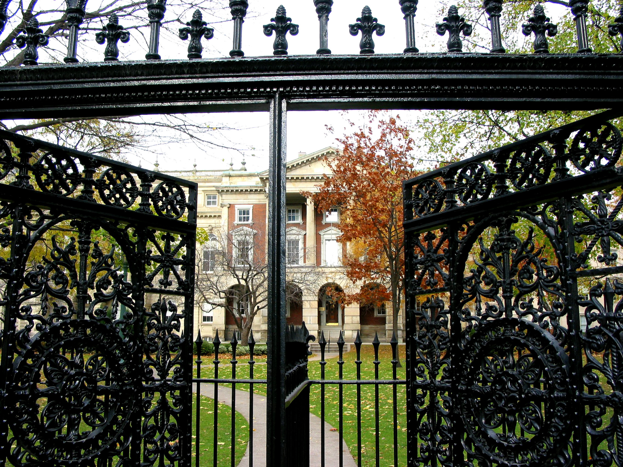 A beautiful wrought iron gate opening to reveal a grand estate